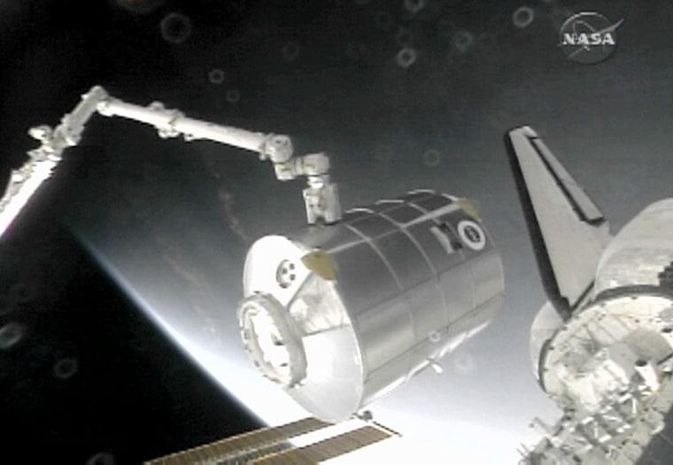 Image: The International Space Station's robotic arm removes the Leonardo Multi Purpose Logistics Module