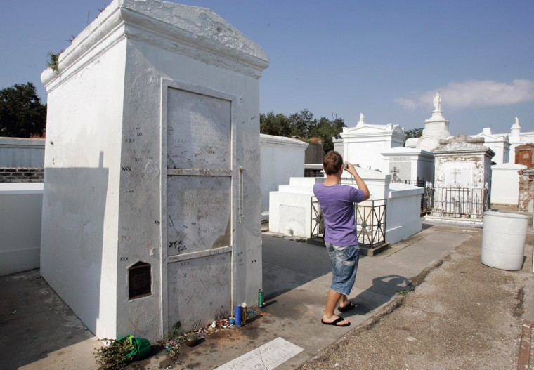 A visitor takes a photograph of St. Louis Cemetery No. 1 with his back to the tomb of famous voodoo queen Marie Laveau on the edge of the French Quarter in New Orleans.