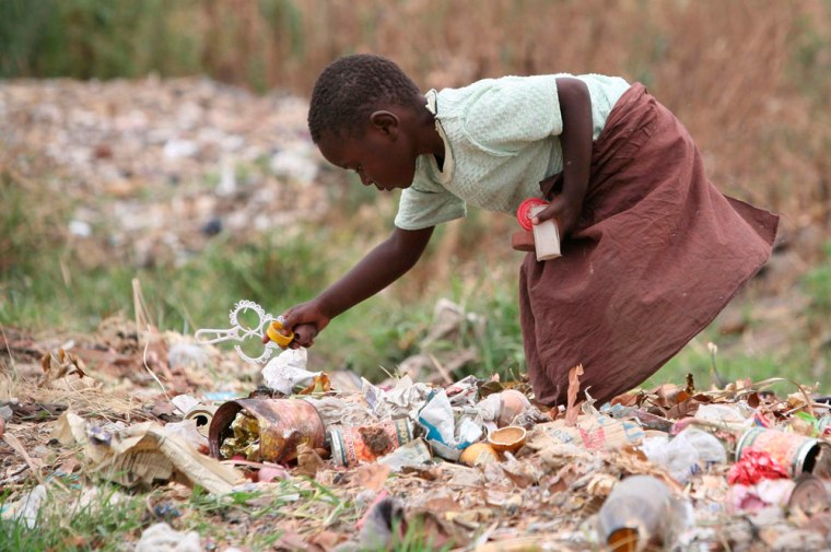 Image: A young girl  scavenges for food in a rubbish dump