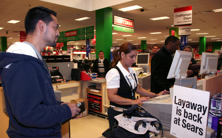Image: Eduardo Galindo places items in layaway at a Sears store