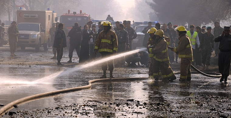 Image: Afghan firefighters wash the road at the site of a suicide attack in Kabul