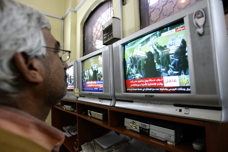 Image: An Iraqi man watches a row of televisions