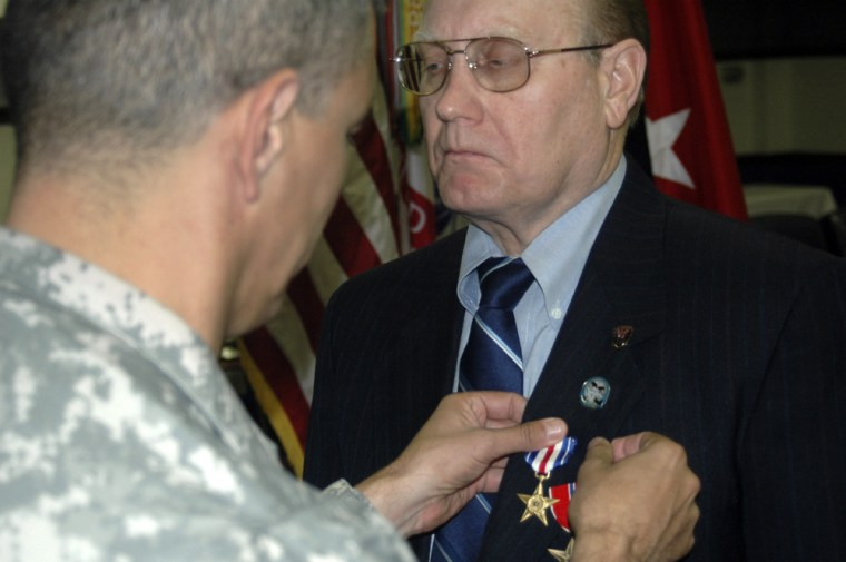 Brig. Gen. Steve Townsend, left, pins the silver star on the lapel of retired Staff Sgt. Gary Harris, 60, Friday,at Fort Campbell,Ky. Harris and his son, Chief Warrant Officer 2 Jonathan Harris, 35, were presented the Silver Star simultaneously.