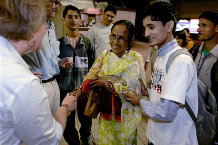 Chitra Gautam, 19, right, introduces his mother, Jamuna Gautam, 36, center, to Catholic Charities representative Clare Kushman, left, as his father Dina Gautam, 40, stands behind him after their arrival at the Greater Pittsburgh International Airport in Imperial, Pa., Monday, Sept. 22.
