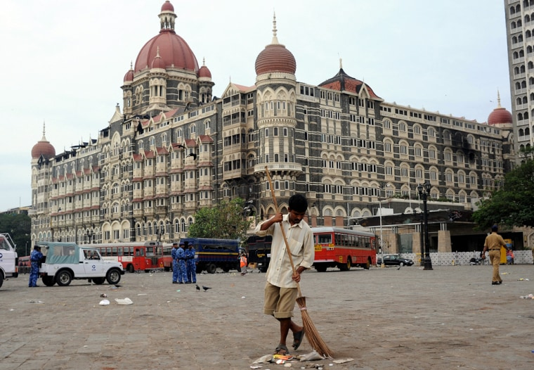 Image: An Indian worker sweeps the street in front of the Taj Mahal Hotel