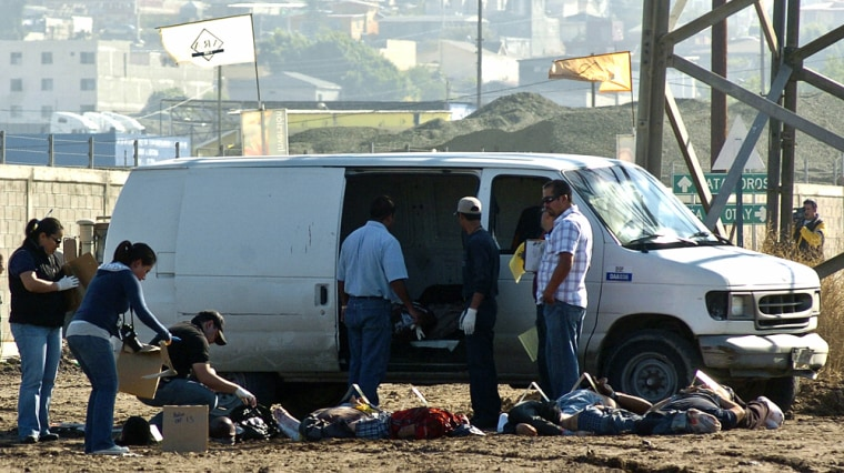 Image: Mexican police officers search the area of nine beheaded bodies found in Tijuana city
