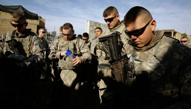 Image: U.S. Army soldierspray before heading out on patrol in Baqouba.
