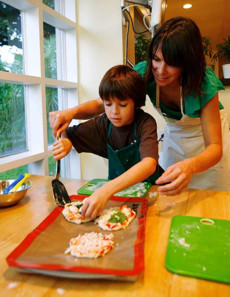 Image: Mimi Chacin helps her son Diego, 9, place home made pizzas onto a tray while cooking dinner at her home in Miami Shores, Fla.