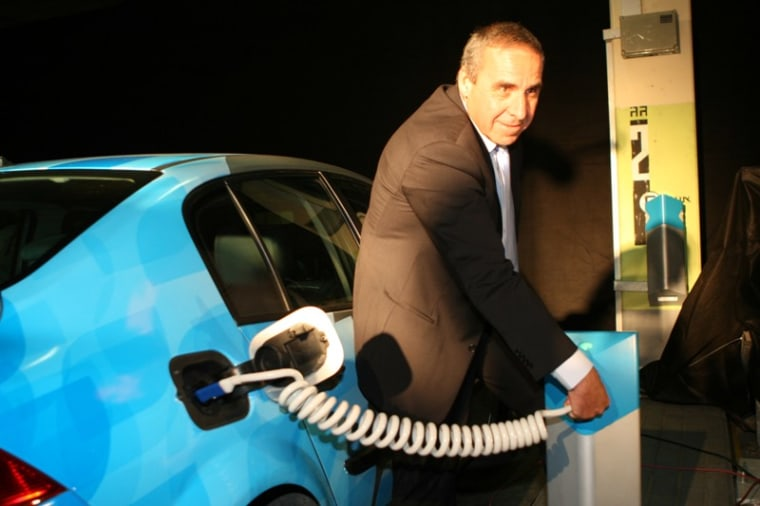 Better Place Israel CEO Moshe Kaplinsky plugs into an electric vehicle charging station in Tel Aviv on Monday.