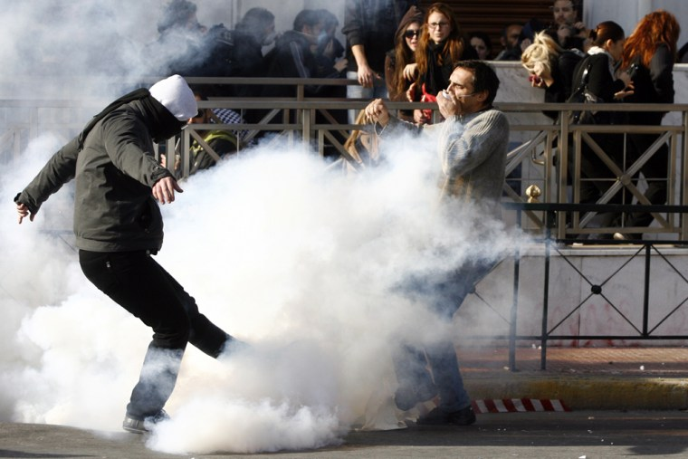 Image: A Greek youth kicks a tear gas away during clashes with riot police