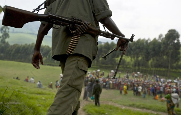 Image: An FDLR soldier walks toward a distribution center near Lushubere Camp in Masisi in the DRC
