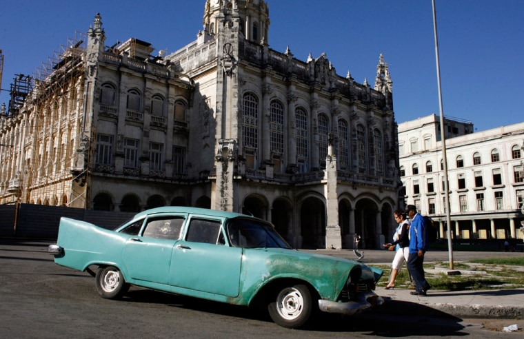 Image: People walk by a classic car parked outside the Revolution Museum in Havana