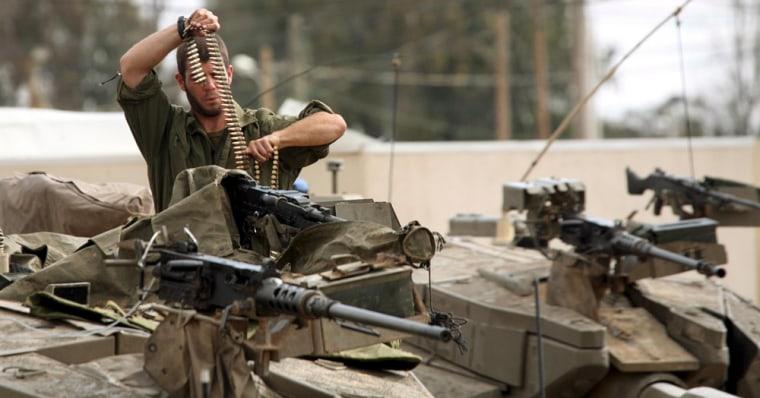 Image: Israeli soldiers prepare tanks on base along Gaza Strip border