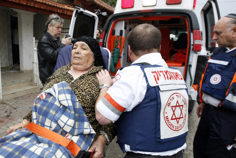 Image: Israeli paramedics evacuate an Israeli woman in shock following a rocket attack on the southern Israeli city of Sderot