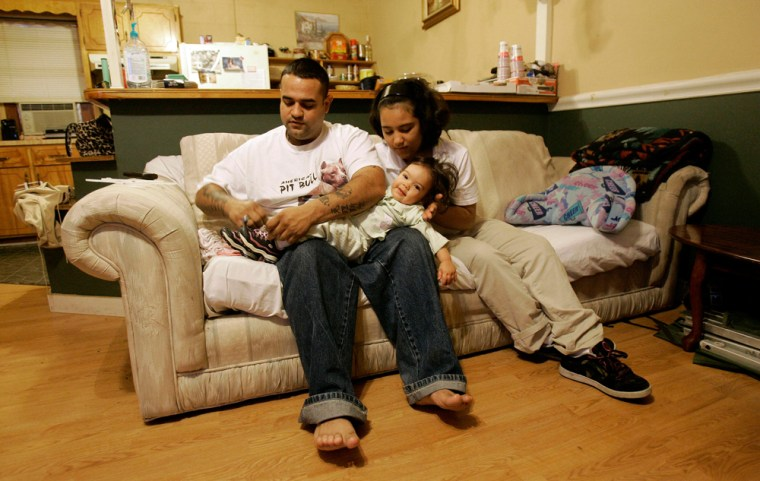 Jobel Barbosa dresses his daughter Annalise Nov. 24, while his 9-year-old daughter Christian watches in Hamlet, N.C.