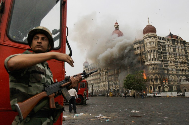 An Indian soldier takes cover as the Taj Mahal hotel burns during gun battle between Indian military and militants inside the hotel in Mumbai, India, Nov. 29, during three days of terror that left more than 150 people killed.