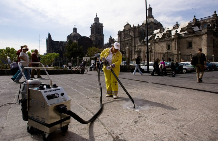 Image:  worker using a sidewalk steam-cleaner removes chewing gum in Mexico City