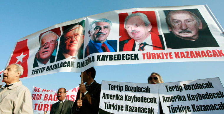 Image: Protesters carry a banner with the portraits of the defendants in coup plot