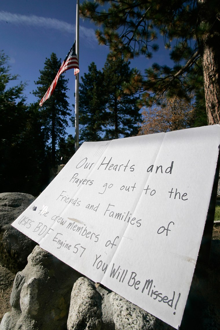Image: The U.S. flag flies at half-staff behind a sign in memory of firefighters who died in the Esperanza fire