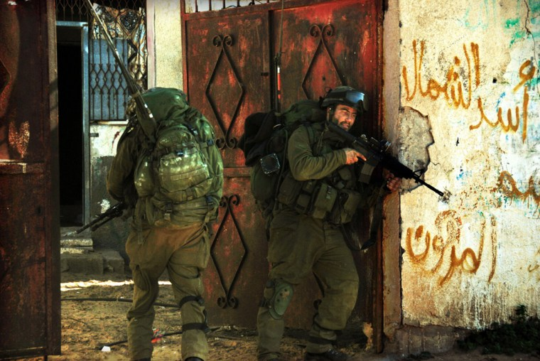 In this handout photo released by the Israeli Army, Israeli soldiers patrol an undisclosed location inside the Gaza Strip, Jan. 7.