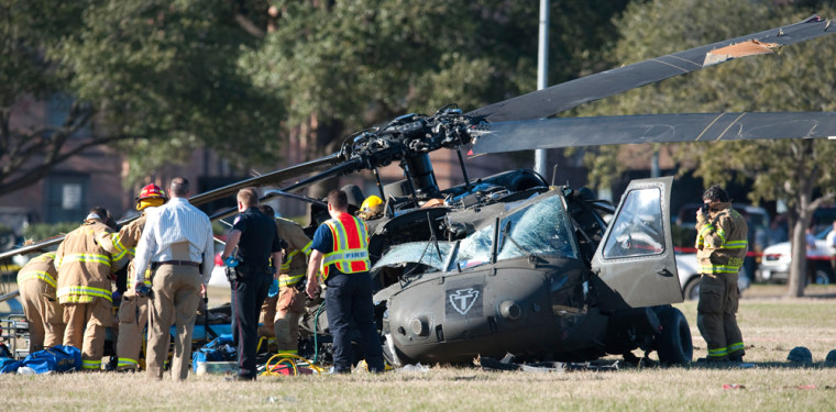 Image: Officials examine the scene of a helicopter crash