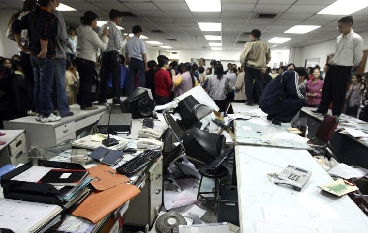 Image: Factory workers occupy an office after smashing equipment during a protest at the Kaida toy factory
