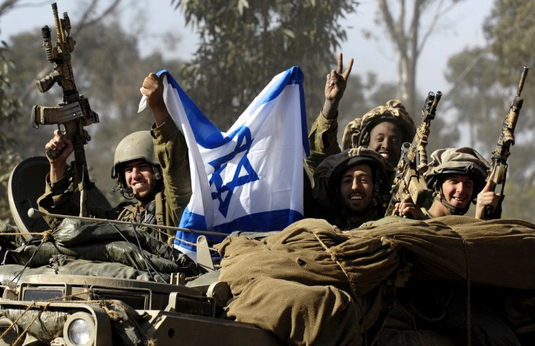 Image: Israeli soldiers hold up national flag