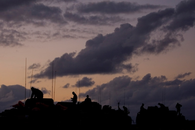 Israeli soldiers operate armored vehicles as they arrive back in Israel after leaving the Gaza Strip, Sunday.