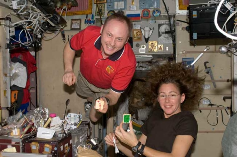 Astronauts Michael Fincke, Expedition 18 commander, and Sandra Magnus, flight engineer, hold Christmas cookies while posing for a photo near the galley in the Zvezda Service Module of the International Space Station. Credit: NASA