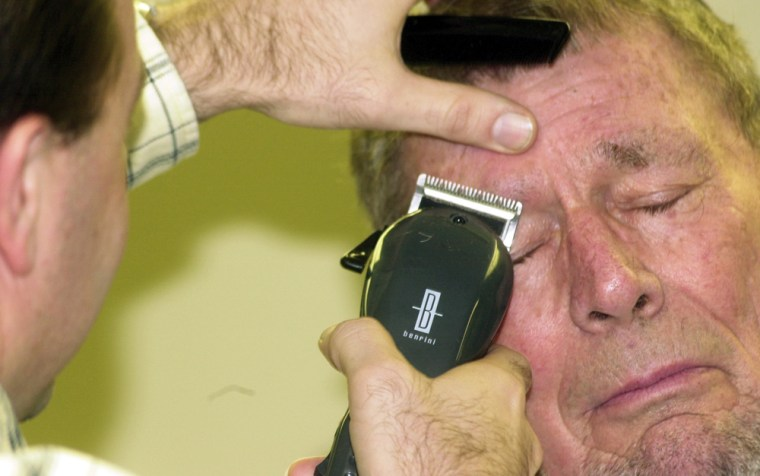 A Bloomfield Rotary Club member shaves off part of Si Burgher's eyebrow in Bloomfield, Ind. Tuesday, Jan. 13, 2009 as part of a fundraiser for Rotary International's PolioPlus project.
