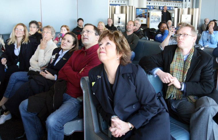 Image: Travelers at Chicago's O'Hare Airport watch President Barack Obama's inaugural