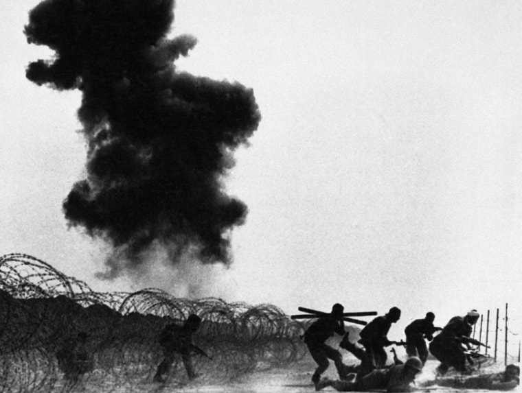 Iranian troops advance through obstacles set by Iraqi forces in the Manjnoon Islands, Iraq, on March 10, 1984. Smoke in the background rises from Iraqi armored units set afire by Iranian forces.