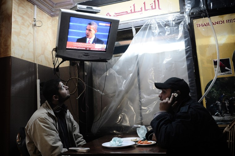 Image: Palestinian youths watch the live televised inauguration ceremony for US President Barack Obama