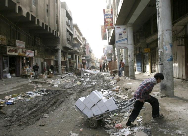 Image: a man pulls a cart through a street