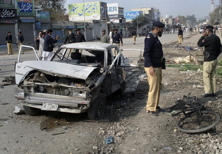 Image: Pakistani police officers examine the site of bomb explosion