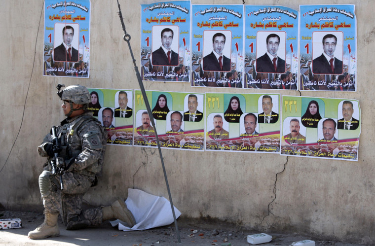 Image: A U.S. soldier kneels beside a wall plastered with provincial election posters