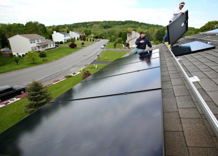 Image: workmen install solar panels