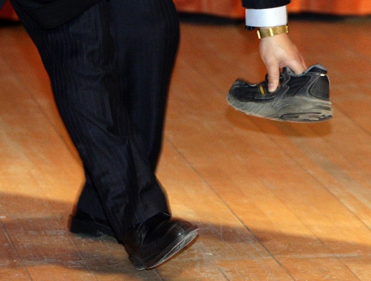 Image: A security guard picks up a shoe that was thrown towards Chinese Premier Wen Jiabao