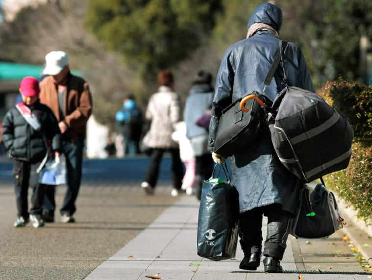 Image: A homeless man walks with his belongings through a park in Tokyo