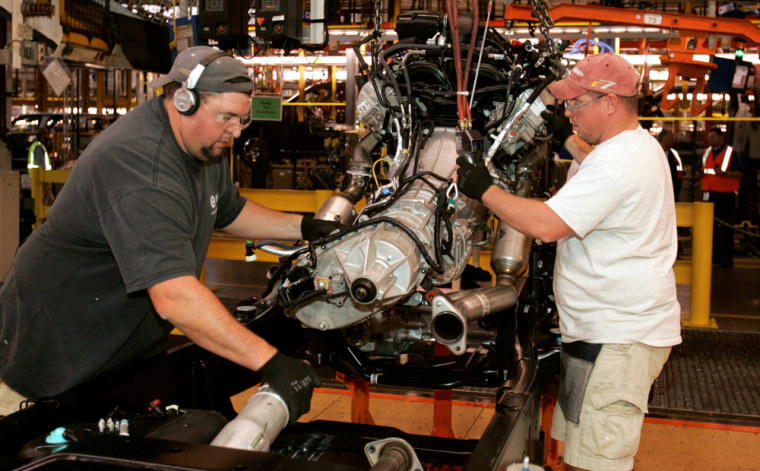 Image: Ford assemblymen mesh the engine to the drive shaft on the 2009 Ford F150 truck.