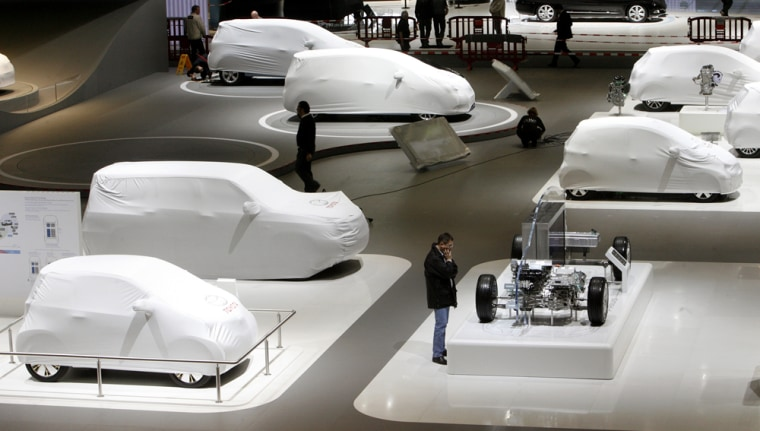 Image: Visitors walk past covered cars