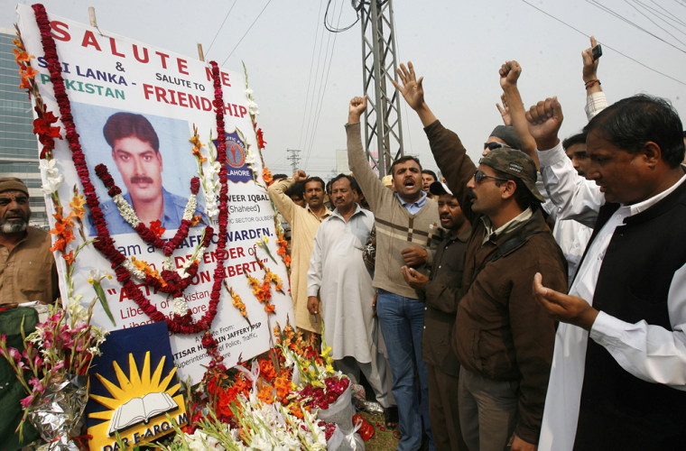 Image: Pakistani people shout slogans as they pray for victims at the site of a shooting in Lahore