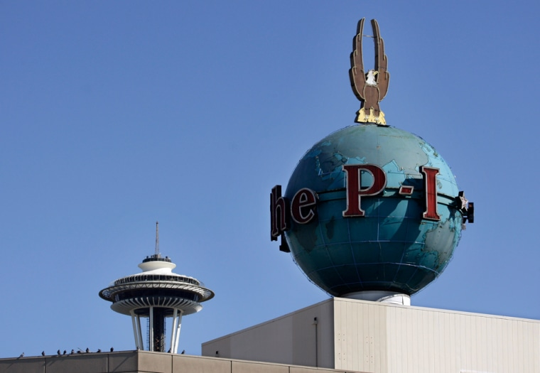 The iconic globe of the Seattle Post-Intelligencer is seen atop the company's waterfront headquarters near the Space Needle, in background. The 146-year-old paper prints its final edition Tuesday.