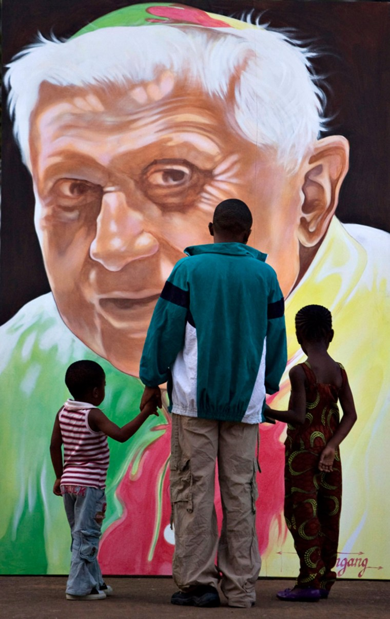 Image: A family looks at a portrait of Pope Benedict in Yaounde, Africa