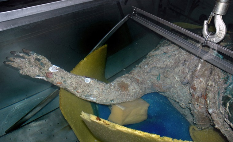 Image: The torso and raised right arm of a 2,200-year-old statue are seen after it was raised in a fisherman's nets.