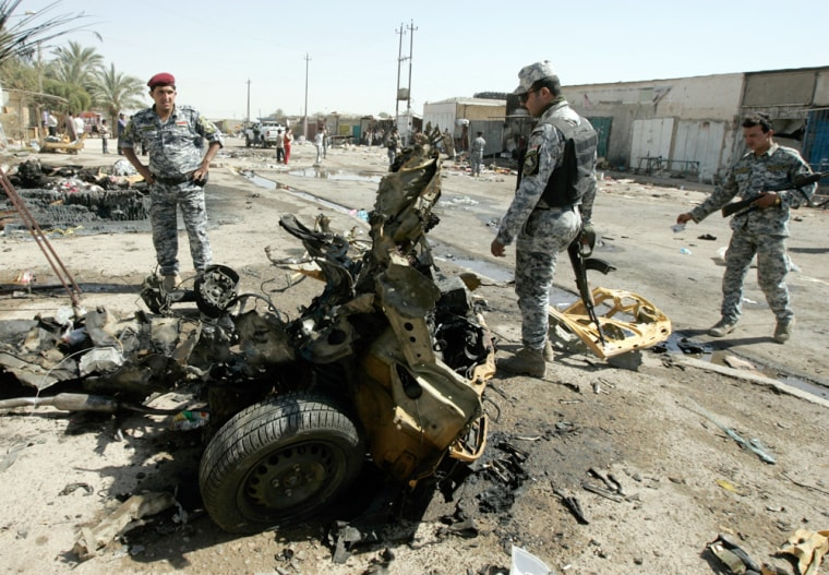 Image: Policemen inspect the wreckage of a vehicle used in a car bomb attack in Baghdad