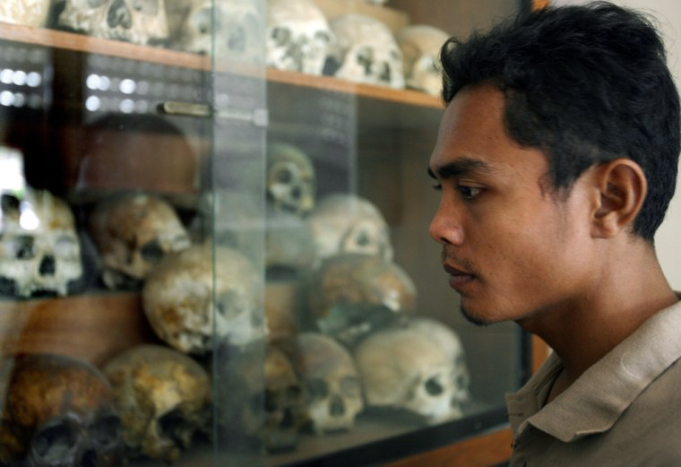 Image: A Cambodian man looks at skulls of the Khmer Rouge victims at Tuol Sleng Genocide museum