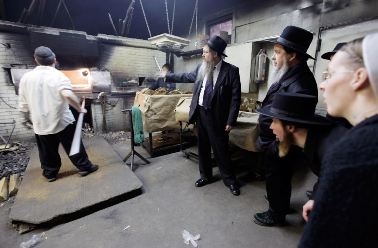 Rabbi Beryl Epstein, center, explains the process of baking matzo for Passover to a group of Pennsylvania Amish Tuesday, March 31, at a matzo factory in the Crown Heights neighborhood of Brooklyn, New York.