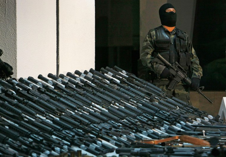 In this Nov. 2008photo, a soldier stands guard during a presentation of seized weapons. Mexico insists the U.S. do more to stop thegun smuggling that is arming the world's most powerful drug cartels with U.S. assault rifles.