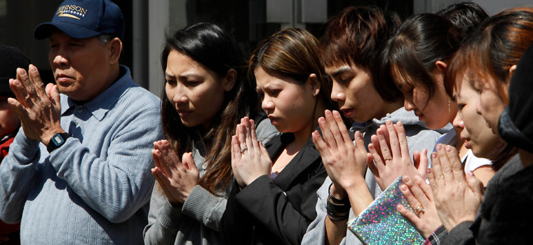 Relatives of shooting victims Lan Ho and Long Huynh pray outside the American Civic Association on Sunday, April 5, in Binghamton, New York.